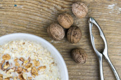 Nueces frescas enteras junto a un cuenco de cereal foto de archivo