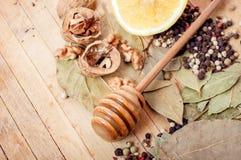 Nueces, miel, pimienta negra, hoja de laurel en una tabla de madera Fotos de archivo