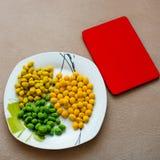 nueces multicoloras en una placa blanca Foto de archivo