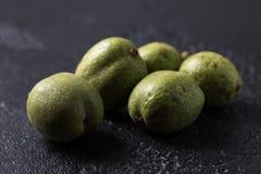 Nueces verdes frescas en la piel apenas del árbol Nueces en un fondo negro Macro Imágenes de archivo libres de regalías