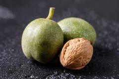 Nueces verdes frescas en la piel apenas del árbol Nueces en un fondo negro Macro Fotografía de archivo