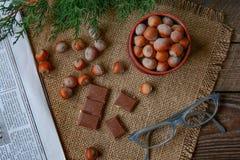 Nueces y chocolate, lectura del periódico Foto de archivo