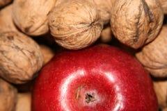 Nueces y manzana roja Imagenes de archivo