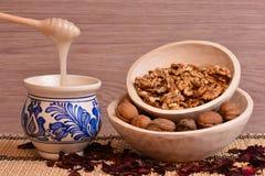 Nueces y miel en el cuenco de madera Fotos de archivo libres de regalías