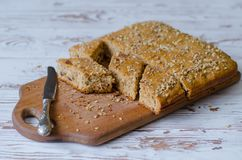 Nueces y torta de miel hechas en casa con el cuchillo que miente cerca en superficie de madera foto de archivo
