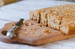 Nueces y torta de miel hechas en casa con el cuchillo que miente cerca en superficie de madera imagen de archivo
