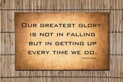 Nuestra gloria más grande - cita de Confucio Imagen de archivo