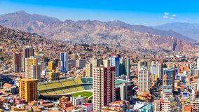 Nuestra Senora de La Paz colorful city town center with skyscrap. Ers, footbal stadium and lots of living houses scattered on the hills with Andes mountains in royalty free stock photography