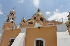 Nuestra Senora de Los Remedios. The side wall of the orange Nuestra Senora de Los Remedios church with its two towers and adorned dome. Cholula, neighbourhood of Stock Image