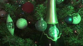 Nueva botella conveniente de champán contra la perspectiva de adornado con juguetes y una guirnalda de un abeto de la Navidad almacen de video
