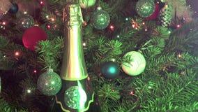 Nueva botella conveniente de champán contra la perspectiva de adornado con juguetes y una guirnalda de un abeto de la Navidad almacen de metraje de vídeo