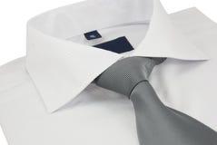Nueva camisa con una corbata rayada gris en un blanco Fotografía de archivo libre de regalías