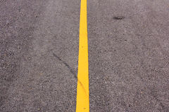 Nueva carretera de asfalto con la línea amarilla antes de la puesta del sol Imágenes de archivo libres de regalías