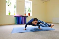 Nueva clase de la yoga del uso de la madre para revivir dolor en espina dorsal Foto de archivo libre de regalías