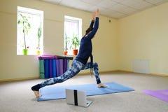 Nueva clase de la yoga del uso de la madre para revivir dolor en espina dorsal Fotografía de archivo libre de regalías