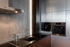 Nueva cocina moderna con construido en golpecito de agua de la capilla, del horno y del cromo del extractor Iluminación del workt imagen de archivo