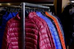 Nueva colección abajo de chaquetas en suspensiones en el mercado Cierre para arriba Imagen de archivo