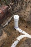 Nueva línea del tubo de alcantarilla del PVC instalada en foso fotos de archivo libres de regalías