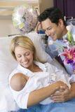 Nueva madre con el bebé y el marido en hospital Imagen de archivo libre de regalías