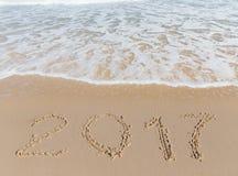 Nueva muestra de 2017 años en una arena de la costa de mar Imagenes de archivo