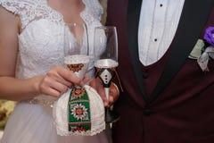 Nueva pareja casada que tuesta los vidrios del champán en el banquete de boda Foto de archivo libre de regalías