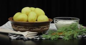 Nueva patata deliciosa hervida en la placa en la tabla preparada Eneldo, crema agria metrajes