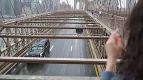 NUEVA YORK, LOS E.E.U.U. - 5 DE MAYO DE 2019: Puente de Brooklyn en la lluvia, muchacha que mira el camino almacen de video