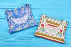 Nuevas camisetas coloreadas, fondo azul Fotos de archivo