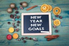 Nuevas metas del Año Nuevo Fondo de la Navidad y del día de fiesta Ornamentos y decoración en una tabla de madera Foto de archivo