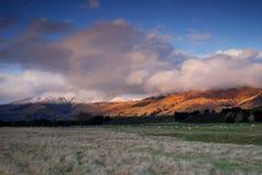 Nuevas montañas de Zealands cubiertas en nubes en la puesta del sol fotos de archivo