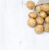Nuevas patatas en un saco en un fondo de madera blanco (con el espacio Fotografía de archivo libre de regalías