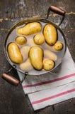 Nuevas patatas frescas en cacerola vieja con agua en fondo de madera rústico Imagenes de archivo