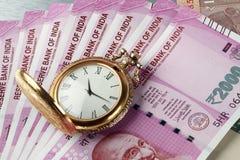 Nuevas rupias indias de moneda con el reloj antiguo del tiempo foto de archivo libre de regalías