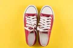 Nuevas zapatillas de deporte rojas en fondo amarillo con el espacio de la copia Fotos de archivo libres de regalías