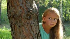 Nueve años de la muchacha ocultan detrás de un árbol, gesticulando silencio Cierre para arriba almacen de video