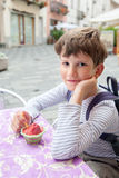 Nueve años de muchacho que come el helado de la baya Imagenes de archivo