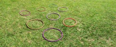 Nueve 9 aros del hula en una hierba verde Fotografía de archivo libre de regalías