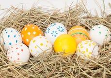 Nueve huevos de Pascua manchados en el heno Foto de archivo libre de regalías