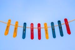 Nueve pinzas plásticas que cuelgan en la cuerda para tender la ropa Fotografía de archivo