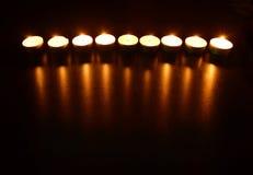 Nueve velas ardientes con la reflexión Imagen de archivo libre de regalías