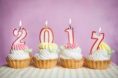 Nuevo 2017 años feliz con las velas en las tortas con el fondo rosado Fotos de archivo