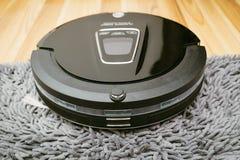 Nuevo aspirador limpio del robot en piso de madera laminado fotografía de archivo