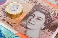 Nuevo billete y monedas de diez libras fotografía de archivo
