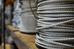 Nuevo cable de acero limpio, alambre de acero o herida de la cuerda de acero en una situación de las bobinas en un estante foto de archivo