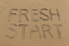 Nuevo comienzo escrito en la arena Foto de archivo