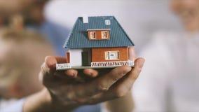 Nuevo concepto casero - familia joven con el modelo de escala de la casa ideal en manos metrajes