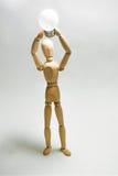 Nuevo concepto de la idea Figura de madera del hombre y bulbo eléctrico ligero imagenes de archivo