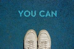 Nuevo concepto de la vida, los zapatos y la palabra USTED del deporte PUEDE escrito en la tierra de la calzada, lema de motivació libre illustration