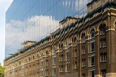 Nuevo contra viejo - un edificio de ladrillo viejo reflejado en ventanas de m fotografía de archivo
