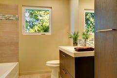 Nuevo cuarto de baño moderno beige con los gabinetes y la tina de madera marrones. Foto de archivo libre de regalías